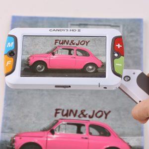 Lupa eletrônica de 5 polegadas, possui 2 botões grandes do lado direito da tela e dois botões grandes do lado esquerdo da tela, possui um cabo para segurar a lupa e cor branca.