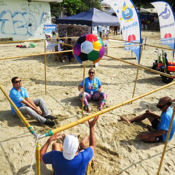 foto de quatro pessoas sentadas na areia com estrutura de barras em volta, com uma bola ao alto