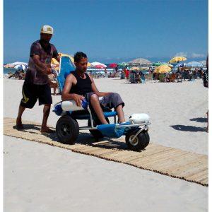 foto de homem sendo empurrado por outro, sentado em cadeira de rodas na praia em cima de esteira de bambu