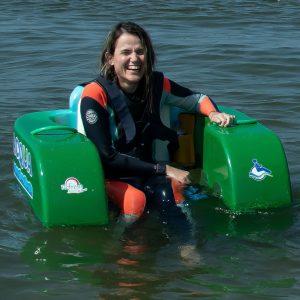 mulher sorrindo em cadeira boiante no mar