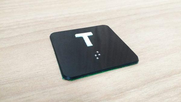 foto de placa quadradra preta com a letra Te em branco e braille em baixo da letra também em branco