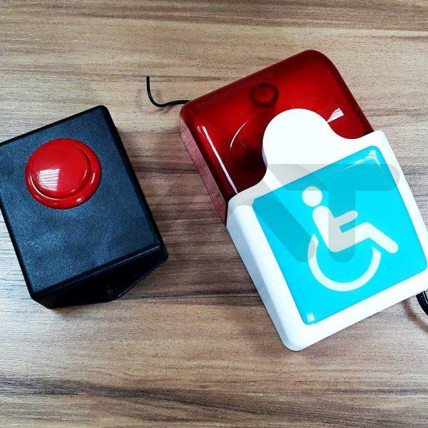 alarme composto por caixa preta com botão azul, e outra caixa com o símbolo da deficiência física, em cima de chão de madeira