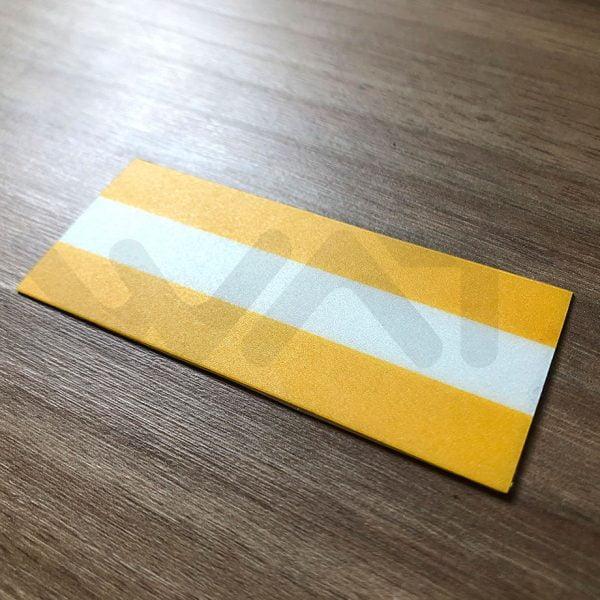 faixa de degraus em três listras, duas amarelas nas pontas e uma faixa branca no meio, apoiado em chão de madeira