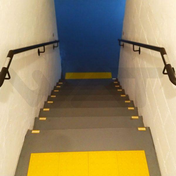 faixa amarela no inicio de uma escada e nos lados próximo à parede, com corrimão e porta azul