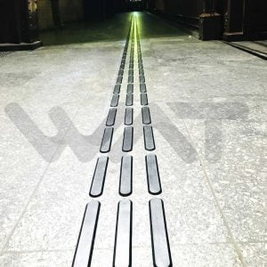 foto de piso tátil com três colunas em chão cinza