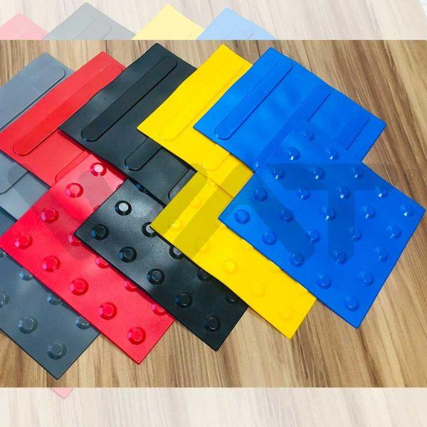 foto de pisos táteis em borracha de cores variadas em chão de piso de madeira