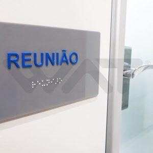 """placa em acrílico cinza com escrito """"reunião"""" em azul e braille em baixo em branco, placa afixada em parede ao lado de uma porta"""