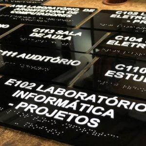 foto de várias placas em acrílico pretas com escritos com palavras em branca e braille logo abaixo