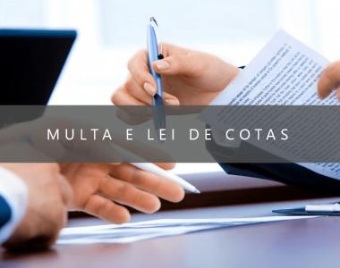 foto das mãos de duas pessoas sentadas em uma mesa de escritório, segurando canetas e papéis, com o escrito: multa e lei de cotas