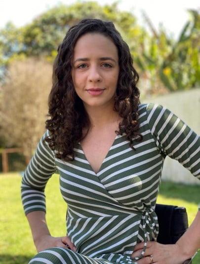 foto de aline adams, mulher de cabelo cacheado e vestido listrado