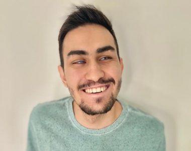 gustavo torniero sorrindo, com camiseta verde, homem branco de barba e cabelo curto