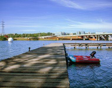 foto de parque com lago e caiaque e caminho de madeira