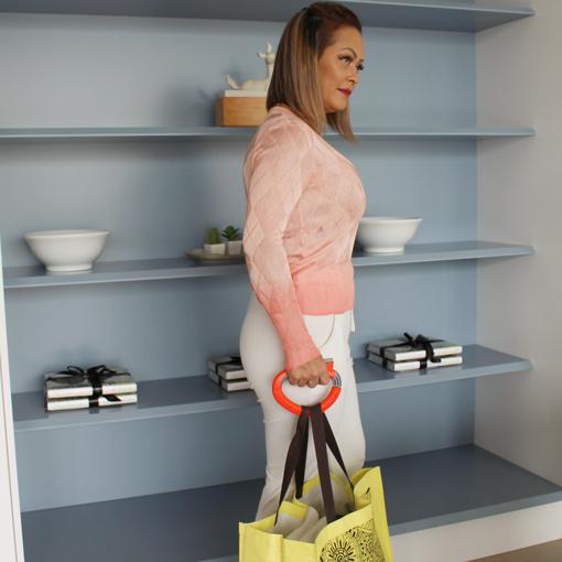 Mulher com Blusa Rosa Usando a Alça Laranja de Segurar Sacolas