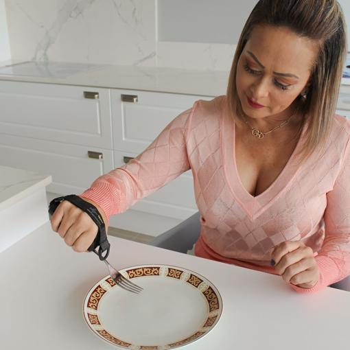 Mulher com Blusa Rosa Usando Adaptador Universal de Utensílios Preto para Comer