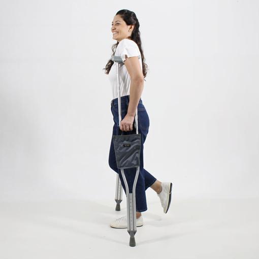 Mulher com Camiseta Branca Usando a Muleta com a Bolsa com Alça Preta