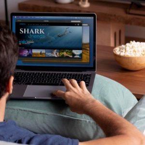 Foto de um homem no sofá, selecionando um filme na netflix, com pipoca na mesa