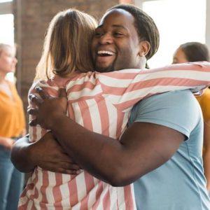 Mulher branca abraçando um homem negro que está sorrindo