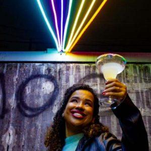 Foto de uma mulher de pele negra, cabelos cacheados, deficiente visual, sorridente segurando uma taça de drink