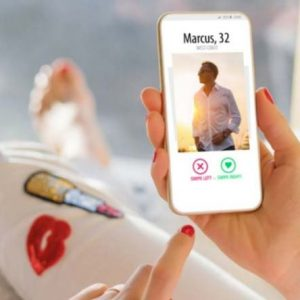 Foto de uma pessoa segurando o celular utilizando aplicativo de paquera