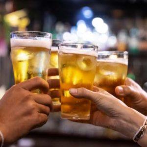 Imagem de mãos segurando um copo de cerveja e brindando