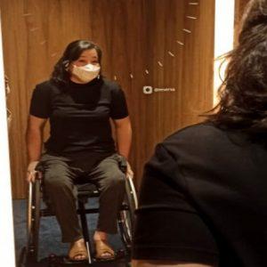 Mulher de pele branca, cabelos pretos curtos, usa máscara, sentada na cadeira de rodas em um provador de loja