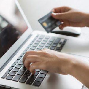 imagem de notebook e uma pessoa digitando com um cartão de crédito na mão